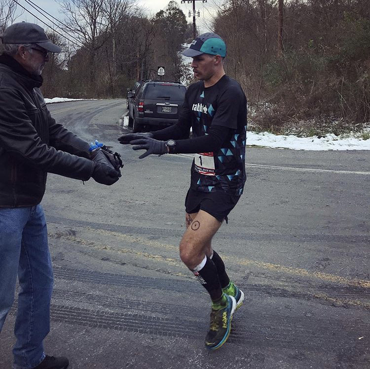 Eric leads JFK 50 coming off the Appalachian Trail and grabs a fresh bottle from his Dad. Photo credit Jacky Cooney.